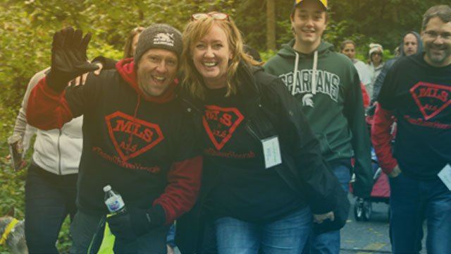 Learn More About Us: Couple waving at the Walk N' Roll 2018